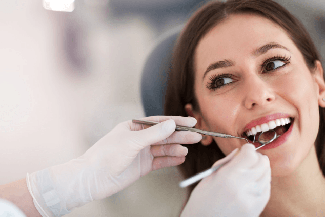 Smiling young female dental implant patient receiving dental implant consultation